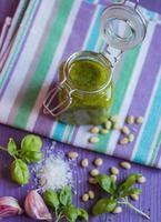 Green pesto in a glass jar and ingredients