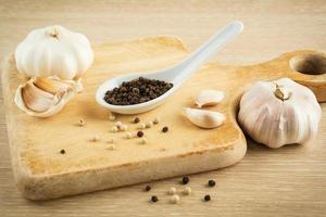 Black peppercorns on spoon and garlic