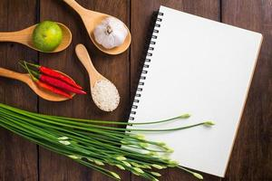 Recipe notebook, rice, Red chilli, garlic and lemon on wood
