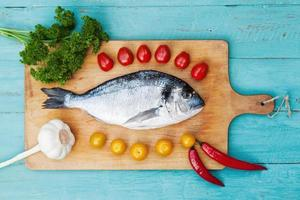 gilthead with ingridients on a chopping board photo