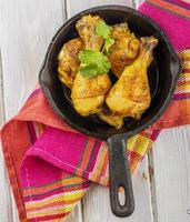 Roasted chicken drumsticks in  pan on a wooden background photo