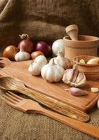 Garlic on cutting board , close-up on sacking. burlap background photo