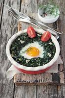 Fresh baked egg with spinach and tomato