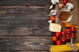 Pasta, tomatoes and mushrooms on wooden table background with copy