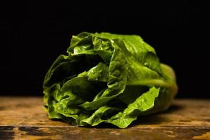 Cos lettuce on wooden table photo