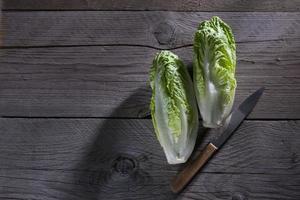 Romaine lettuce and knife on wood photo