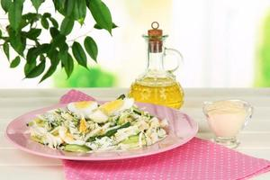 Delicious salad with eggs, cabbage and cucumbers on table photo