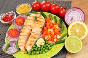 Tasty grilled salmon with vegetables, close up photo