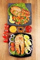 Tasty grilled salmon with lemon and vegetables, on wooden table photo