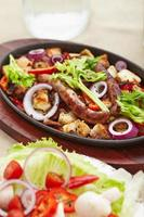pollo asado en cubitos y salchichas con ensalada de tomates foto