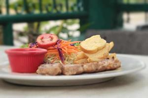 bifes e salada de legumes com batatas fritas.
