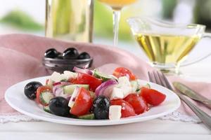 Greek salad served in plate with wine on table photo