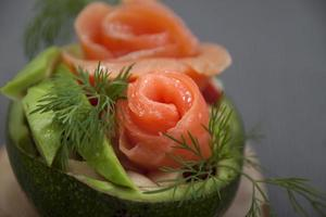 Salad with salmon in half avocado    .