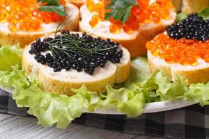 Sandwiches with red and black caviar on lettuce