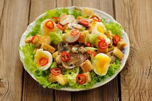 Salad Caesar with mushrooms, eggs, chili and radish on wooden