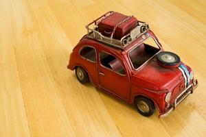 Old red toy car on a wooden floor.