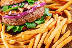 Burger and french fries close up on wooden background.