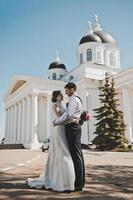 The couple are standing in front of the white columns