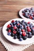 gefrorene Beeren auf Tellern, auf hölzernem Hintergrund