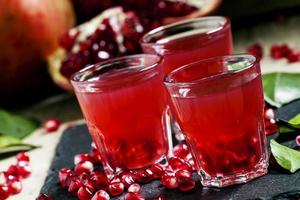 Fresh pomegranate juice on a black background