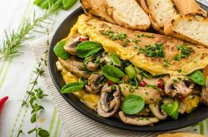 Omelet with mushrooms, lamb's lettuce, herbs and chilli