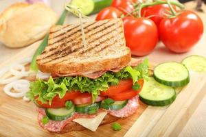 Sandwich with cheese and salami on wood background