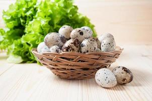 ovos de codorna em uma tigela de vime e salada verde