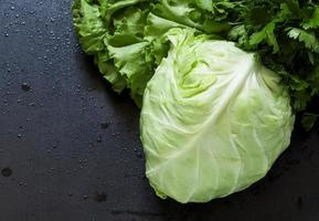 Fresh cabbage, lettuce, parsley on a wooden table, selective foc photo