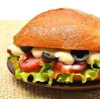 Tasty fresh sandwich with green lettuce, ham, olives on sacking photo