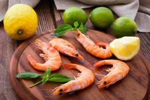 deliciosos camarones frescos mariscos con limón en la mesa de madera foto