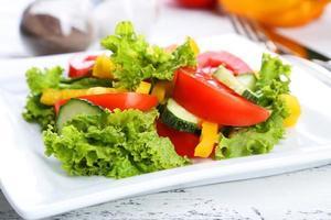 salada de legumes fresca em fundo branco de madeira