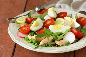 fresh green salad with salmon and tomatoes photo