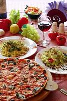 Classic Italian food setting with pizza, pasta, salad and wine