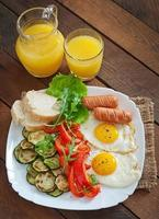 English breakfast - fried eggs, sausages, zucchini and sweet peppers