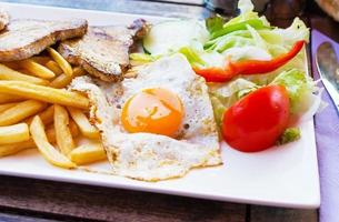 Fried egg with potato fries, grilled steak.