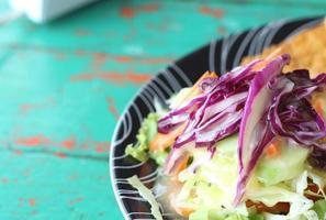 bifes, batatas fritas com salada de legumes em um prato.