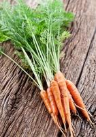 Carrots with leaves on a old wooden table. photo