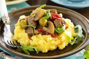 delicioso estofado de ternera con aceitunas, champiñones y polenta. foto