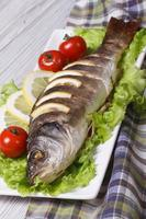 Baked sea bass with lemon, lettuce and tomatoes. vertical
