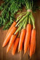 Manojo de zanahorias orgánicas frescas sobre fondo de madera