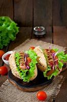 Hotdog with ketchup mustard and lettuce on wooden background.