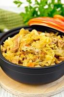 Cabbage stew with meat in black roaster on board photo