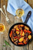 Meat roasted with potatoes, carrots, onions, rosemary and garlic