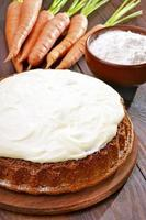 Carrot cake with icing on wooden table