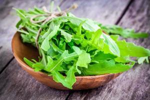 organic arugula bundle in a wooden bowl photo