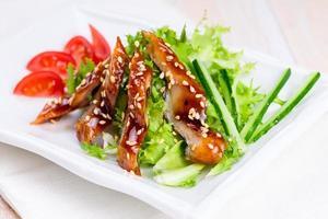 Smoked eel with unagi sauce and sesame seeds