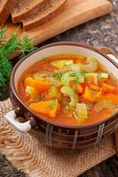 Vegetable soup on the old wooden background photo