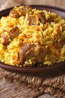 pilaf with meat and vegetables closeup on a plate. Vertical