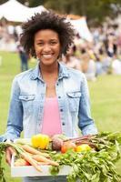Mujer sonriente sosteniendo una bandeja blanca llena de begetables frescos foto