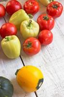 Tomatoes, pepper and zucchini on white wooden surface